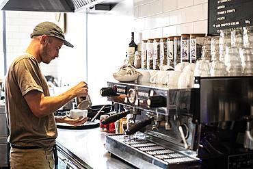 Bearded man wearing baseball cap standing at espresso machine a restaurant