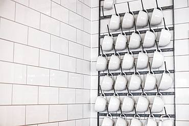 Close up of white cappuccino mugs hanging on a metal rack on white tiled wall