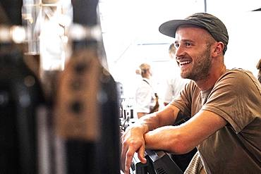 Portrait of bearded man wearing baseball cap standing in a cafe, smiling