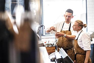 Male and female chef wearing brown aprons standing at a counter, checking an order