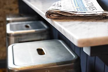 Close up of three stools at a bar counter, folded newspaper on top