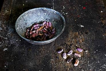 High angle close up of grey metal bowl with purple speckled beans on wooden table