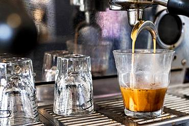 A commercial expresso machine in a coffee shop making an expresso shot