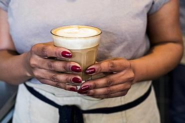 Woman barista preparing a cup of coffee in a coffee shop