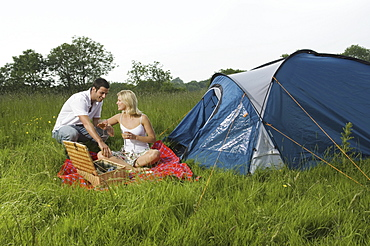 A couple, a man and woman seated having a picnic. A blue tent. Camping, England