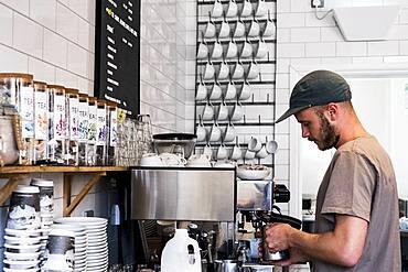 A man barista working a coffee machine in a cafe