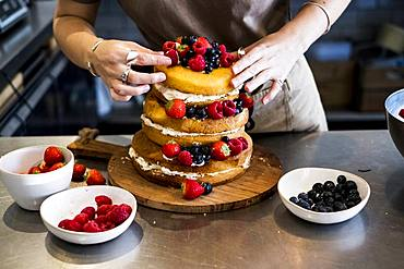 a cook working in a commercial kitchen arranging fresh fruit over a layered cake with fresh cream