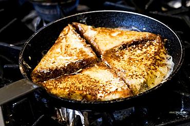A frying pan on the hob, with eggy bread or croque monsieur sandwiches being fried