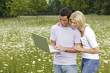 A man and woman in a flower meadow, looking at a laptop screen, England