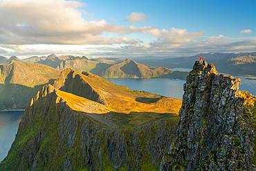 Man standing at the top of a pinnacle with a view over the landscape, Senja Island, Troms, Senja Island, Lofoten Islands, Norway