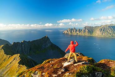 Man with arms spread in celebration on top of mountain, Senja Island, Troms, Senja Island, Lofoten Islands, Norway