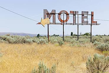 Vintage motel sign with dry scrub-land in foreground, Whitman County, Palouse, Washington, United States of America