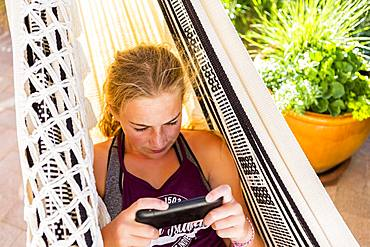 A teenage girl in hammock looking at smart phone, Grand Cayman, Cayman Islands