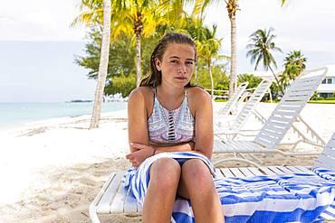 A teenage girl sitting in beach chair, Grand Cayman, Cayman Islands