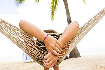 A teenage girl relaxing in a hammock, Grand Cayman, Cayman Islands