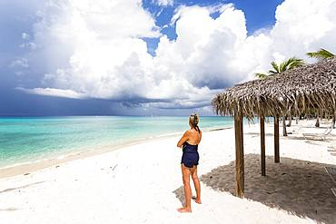 Adult woman watching approaching storm clouds from a beach, Grand Cayman, Cayman Islands