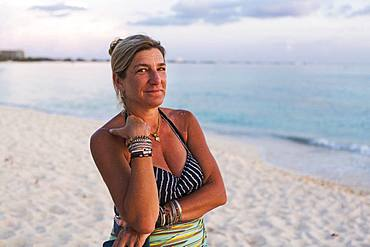 Adult woman looking at setting sun, Grand Cayman, Cayman Islands