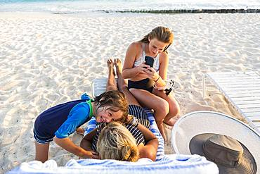Mother and her children enjoying the beach at sunset, Grand Cayman, Cayman Islands