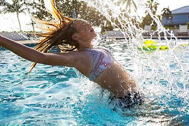 A teenage girl tossing her wet hair back in a swimming pool, Grand Cayman, Cayman Islands