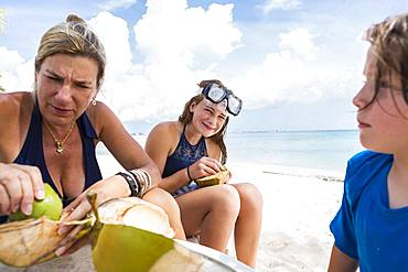 Bother and her kids cutting a coconut on a sandy beach, Grand Cayman, Cayman Islands