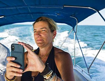Adult woman taking picture with smart phone, on boat, Grand Cayman, Cayman Islands