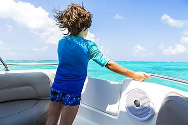 5 year old boy on a boat looking at the ocean, Grand Cayman, Cayman Islands