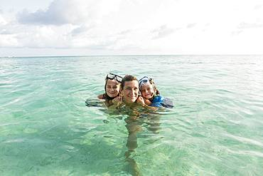 Adult woman standing in ocean water at sunset with her children, Grand Cayman, Cayman Islands