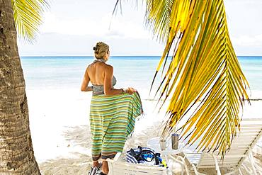 Adult woman wrapping herself in a colorful sarong at the beach, Grand Cayman, Cayman Islands
