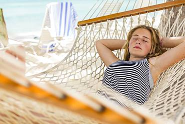 A teenage girl relaxing in a hammock on the beach, Grand Cayman, Cayman Islands