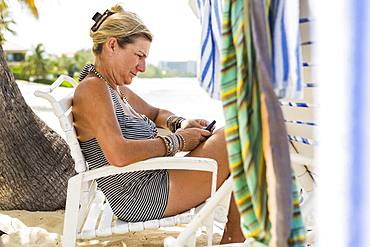 Adult woman executive using a smart phone on the beach, Grand Cayman, Cayman Islands