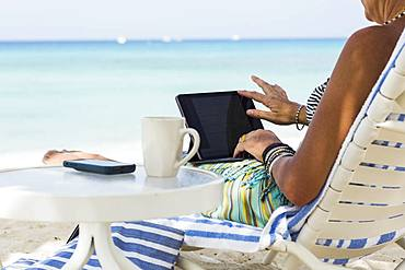 adult woman executive using laptop on the beach , Grand Cayman, Cayman Islands