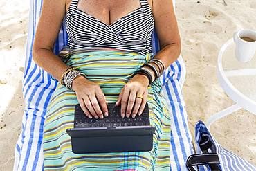 adult woman executive using laptop on the beach, Grand Cayman, Cayman Islands