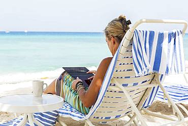 adult woman executive using smart phone on the beach, Grand Cayman, Cayman Islands