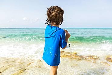 5 year old boy preparing to wear snorkelling mask, Grand Cayman, Cayman Islands