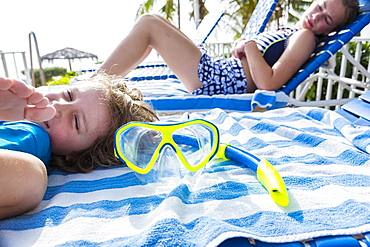 Brother and sister, a teenage girl and a young boy lying on sunbeds, Grand Cayman, Cayman Islands