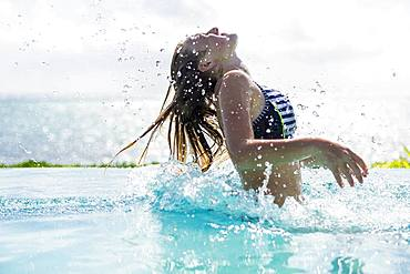 A teenage girl in infinity pool, tossing her hair back, Grand Cayman, Cayman Islands