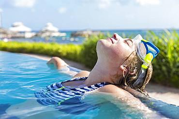 A teenage girl in infinity pool, Grand Cayman, Cayman Islands