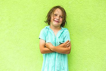 Smiling 5 year old boy posing in front of green wall, Grand Cayman, Cayman Islands