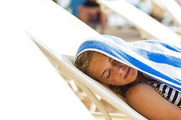 A teenage girl reclining in beach chair with towel on her head, Grand Cayman, Cayman Islands