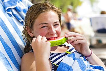 A teenage girl eating watermelon, Grand Cayman, Cayman Islands