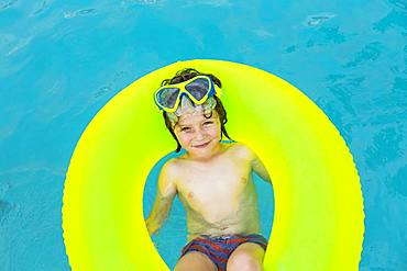 Smiling 5 year old boy in colorful floatie in the water, Grand Cayman, Cayman Islands