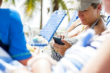 Woman texting on smart phone while on vacation, Grand Cayman, Cayman Islands