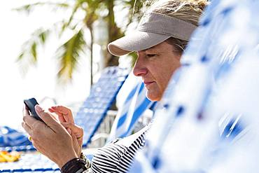 Woman texting on smart phone on vacation, Grand Cayman, Cayman Islands
