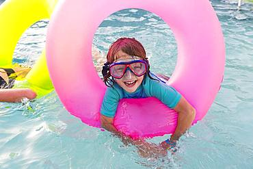 Siblings, brother and sister playing in pool with colorful floaties, Grand Cayman, Cayman Islands