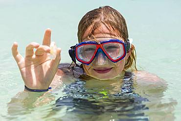 A teenage girl wearing snorkel mask holding sea glass, Grand Cayman, Cayman Islands