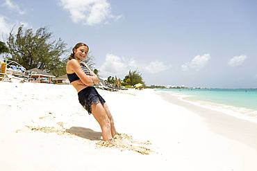A teenage girl leaning in the sand, Grand Cayman, Cayman Islands
