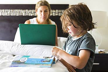 5 year old boy looking at book in hotel room as mom works on laptop, Grand Cayman, Cayman Islands