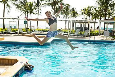 A teenage girl leaping into pool, Grand Cayman, Cayman Islands