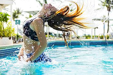 A teenage girl leaping out of the pool, Grand Cayman, Cayman Islands