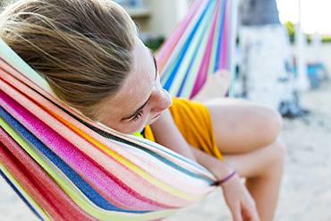 A teenage girl resting in hammock, Grand Cayman, Cayman Islands